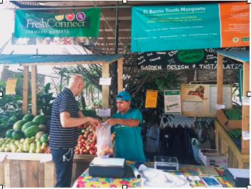 Photo // Charlotte Gibson Adrian Rosado helps local customer Thomas Hirschelmann choose ripe peaches on Thursday, August 28, 2014.